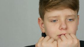 Portrait of a teenager boy who bites his nails and fingers as if showing what he is experiencing or is afraid of on. A white background in the studio. Emotions stock video footage