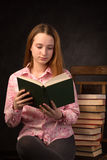 Portrait of a teenager girl reading book near the stack of books. stock image