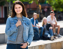 Portrait of  teenager girl standing aside from friends outdoors Stock Photos