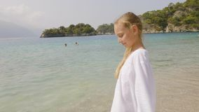 Portrait teenager girl in white dress on blue sea and green mountain landscape. Tourist girl watching sea and mountain. Landscape on summer beach stock footage