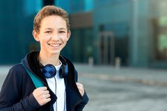 Portrait of a teenager with headphones and backpack outdoors. Copy space royalty free stock images