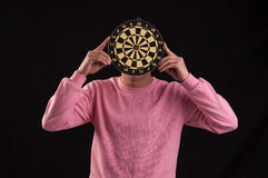 Portrait of teenager holding a dartboard over his face Royalty Free Stock Images