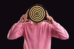 Portrait of teenager holding a dartboard over his face Stock Photo