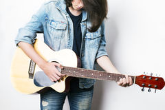Fashion portrait of a teenager playing guitar in studio wearing jeans jacket Royalty Free Stock Photography