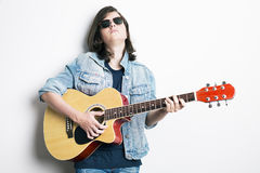 Portrait of a teenager playing guitar in studio while wearing sunglasses and jeans jacket Stock Photo
