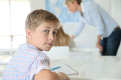Portrait of teenager pupil in class. Young smiling schoolboy in classroom Royalty Free Stock Image