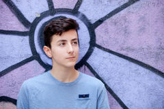 Portrait of a teenager rebellious man. On a wall with graffiti background Royalty Free Stock Image