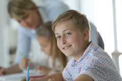 Portrait of teenager schoolboy in class. Young smiling schoolboy in classroom Royalty Free Stock Photo