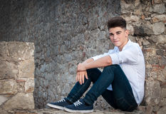 Portrait of a teenager. He is sitting in a stone wall. Dramatic. Portrait Stock Images