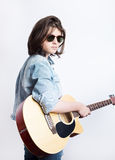 Side view portrait of a teenager wearing sunglasses and jeans jacket in studio background while holding a guitar Royalty Free Stock Photography
