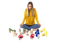 Portrait of a teenager woman sitting on the floor between many pairs of shoes against white. Consumerism concept.  royalty free stock image