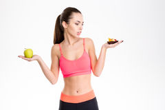 Portrait of tempted attractive fitness woman making food choice Royalty Free Stock Images