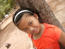 A portrait of ten years  old Thai girl  lean back on pinewood Royalty Free Stock Photos