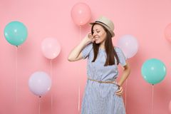 Portrait of tender fascinating young woman wearing straw summer hat and blue dress keeping hand near face on pink. Background with colorful air balloons stock image