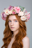Portrait of tender female with wavy hair in flower wreath Stock Images