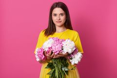 Portrait of tender magnetic black haired lady wearing bright yellow items of clothes, looking directly at camera, having good mood. Holding bouquet of white stock photos