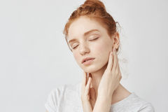 Portrait of tender redhead girl with freckles and closed eyes dreaming of comfort. Over white background. Royalty Free Stock Photography