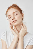 Portrait of tender redhead girl with freckles and closed eyes. Royalty Free Stock Images