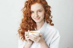 Portrait of tender redhead girl with freckles smiling holding cup looking at camera. White background. Royalty Free Stock Photo