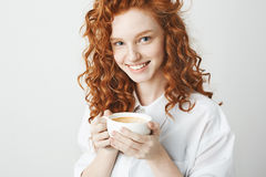 Portrait of tender redhead girl with freckles smiling holding cup looking at camera. White background. Stock Photography