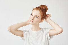 Portrait of tender redhead girl with hair bun and freckles smiling. royalty free stock photography