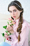 Portrait of tender woman holding roses close to her face Royalty Free Stock Image