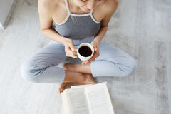Portrait of tender young beautiful girl reading book holding cup of coffee sitting on floor over white wall. From above. Portrait of tender young beautiful girl Royalty Free Stock Images