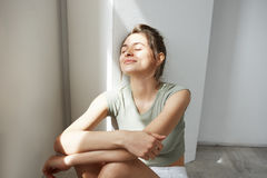 Portrait of tender young beautiful girl smiling with closed eyes enjoying morning sunlights sitting on floor over white. Wall. Copy space Royalty Free Stock Photos
