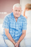 Portrait of tensed senior man sitting on bed Royalty Free Stock Image