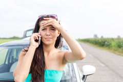 Portrait of tensed woman using cell phone against broken down car on road Stock Image
