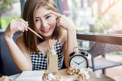 Portrait of thai adult businesswoman beautiful girl. Write a book with trash paper and alarmclock on wooden table in coffee shop royalty free stock images