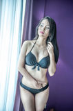 Portrait of thai woman in lingerie posing at window in hotel roo Royalty Free Stock Images