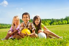 Portrait of thee happy kids with balls royalty free stock images
