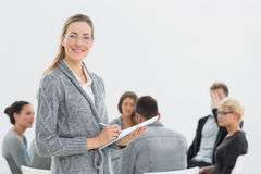 Portrait of therapist with group therapy in session in background. Portrait of a smiling female therapist with group therapy in session in background Stock Image