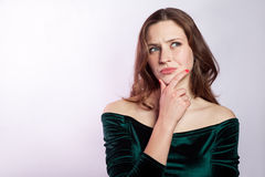 Portrait of thinkful woman with freckles and classic green dress. Royalty Free Stock Photos