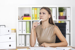 Portrait of a thinking blond woman with marker Royalty Free Stock Photos
