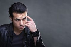 Portrait of a thinking business serious man. Portrait over dark gray background Studio. a man in a black leather jacket. the concept of deception and business royalty free stock photos