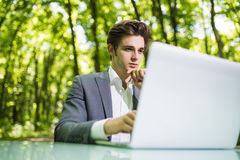 Portrait of thinking Businessman sitting at the office desk work at laptop computer in green forest park. Freelancer with hands on Stock Photo