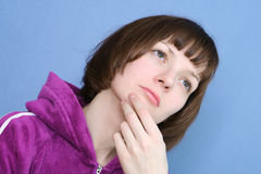 Portrait of thinking female. On a blue background in a jacket Stock Photo