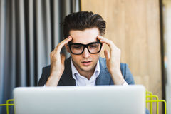 Portrait of thinking man using laptop computer at home. Stock Photos