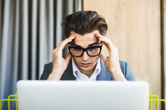 Portrait of thinking man using laptop computer at home. Royalty Free Stock Photography