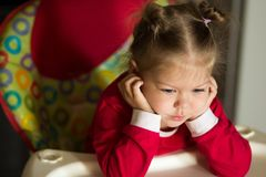 Portrait of thinking and sad little girl propping head by hands royalty free stock images