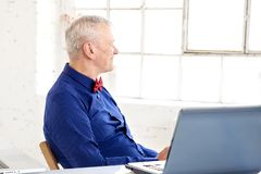 Portrait of thinking senior businessman sitting in the office behind his laptop stock photos