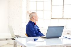 Portrait of thinking senior businessman sitting in the office behind his laptop royalty free stock photography