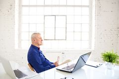 Portrait of thinking senior businessman sitting in the office behind his laptop stock photography