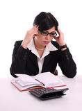 Portrait of a thinking successful business woman. Writing at her desk isolated over white background Stock Image