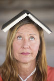 Portrait thinking woman with book on head Stock Photography