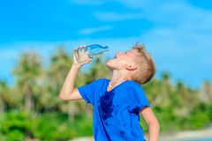 Portrait of a thirsty handsome boy drinking water on the desert. Tropical beach Stock Photo
