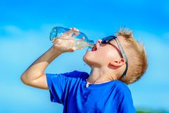 Portrait of a thirsty handsome boy in sunglasses drinking water. On the desert tropical beach Royalty Free Stock Photos