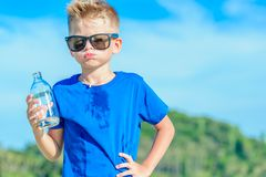 Portrait of a thirsty handsome boy in sunglasses drinking water. On the desert tropical beach Royalty Free Stock Image